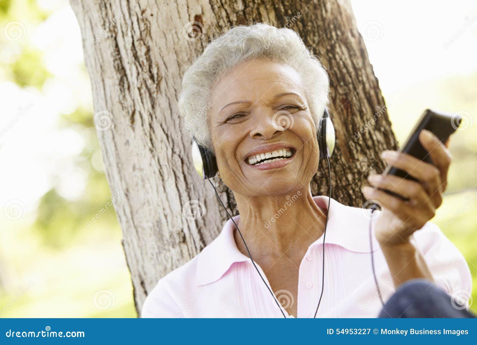 Mulher afro-americano superior na escuta o leitor de mp3