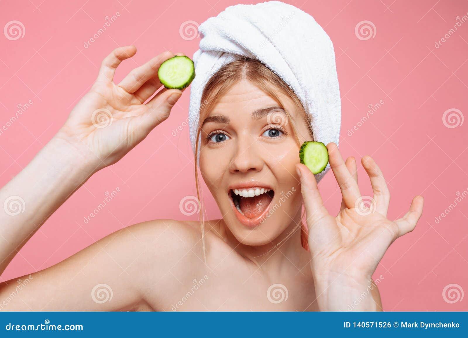 Mulher alegre atrativa com uma toalha envolvida em torno de sua cabeça, guardando fatias do pepino perto de sua cara, em um fundo