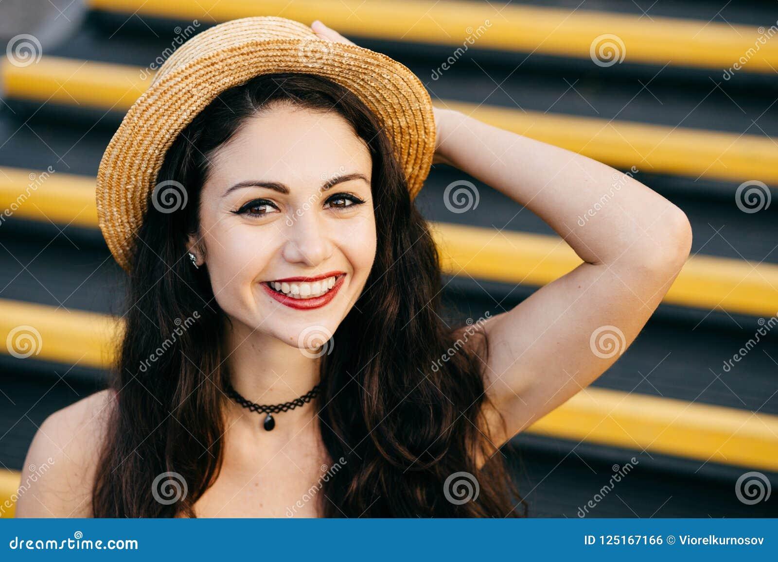 Mulher alegre com cabelo escuro, pele saudável, olhos brilhantes que vestem o chapéu de palha na cabeça que senta-se nas escadas