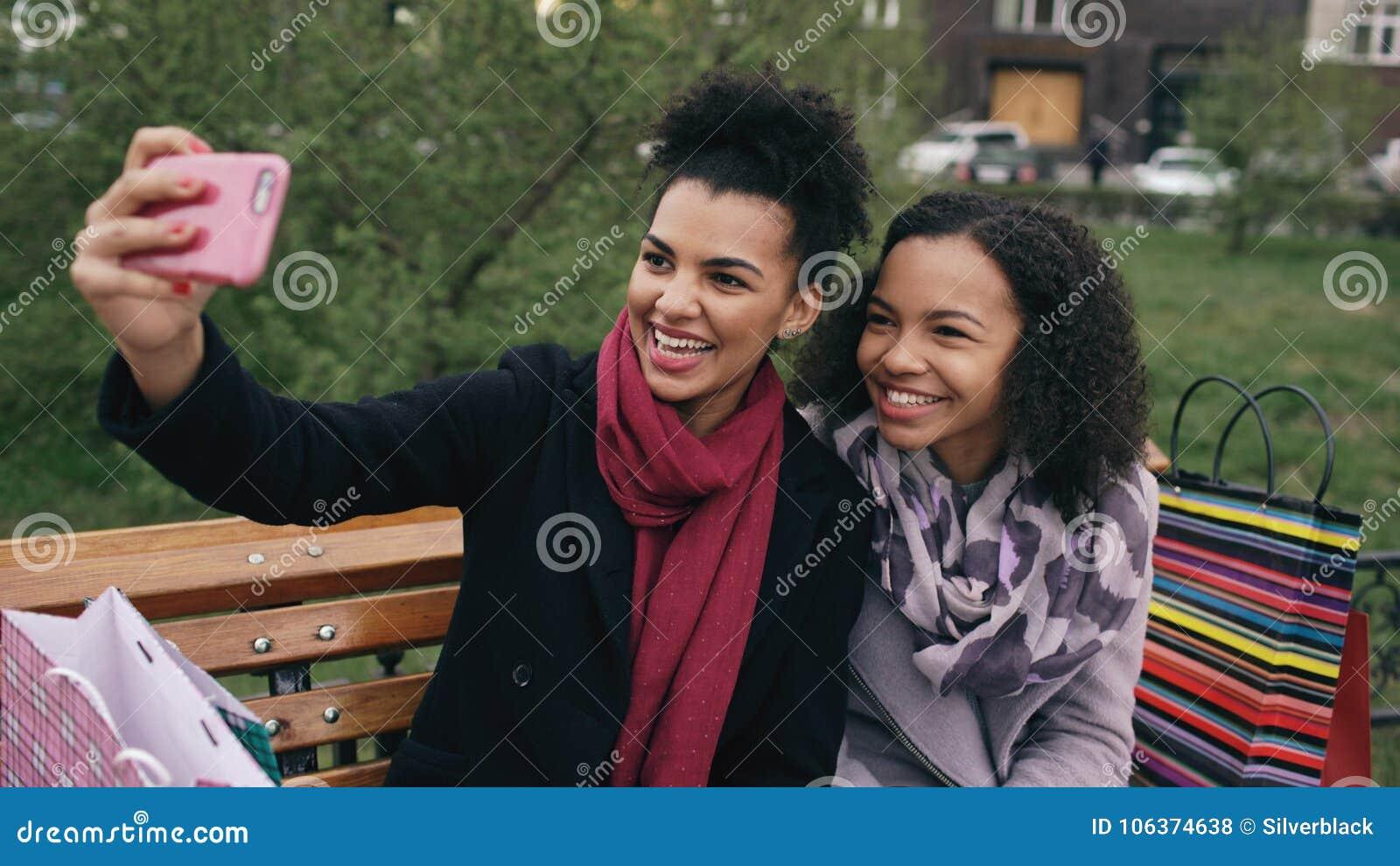 Mulher alegre da raça dois misturada com sacos de compras que fala na chamada video com smartpone As moças que sentam-se no banco