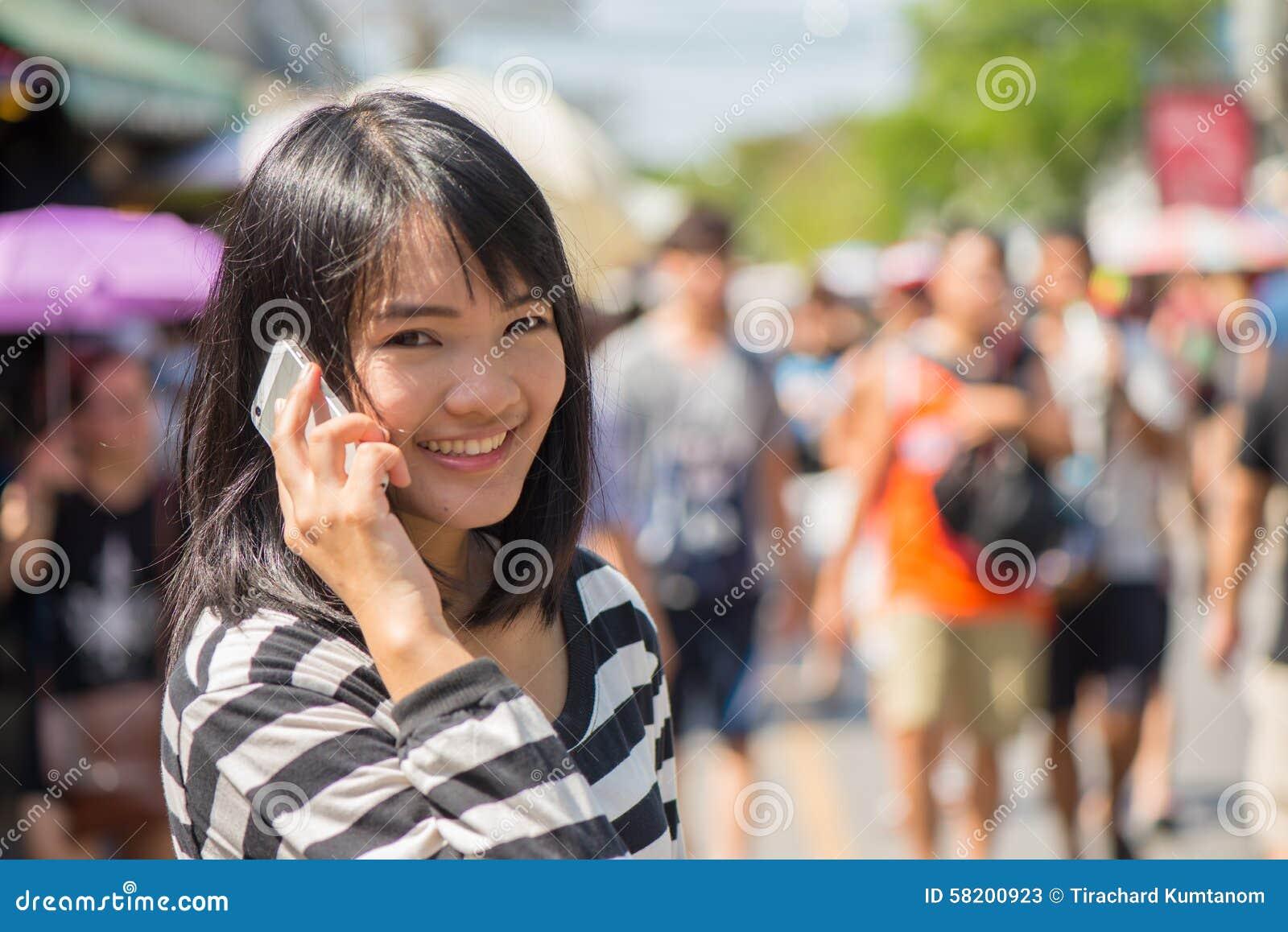 Mulher alegre que fala no telefone na rua