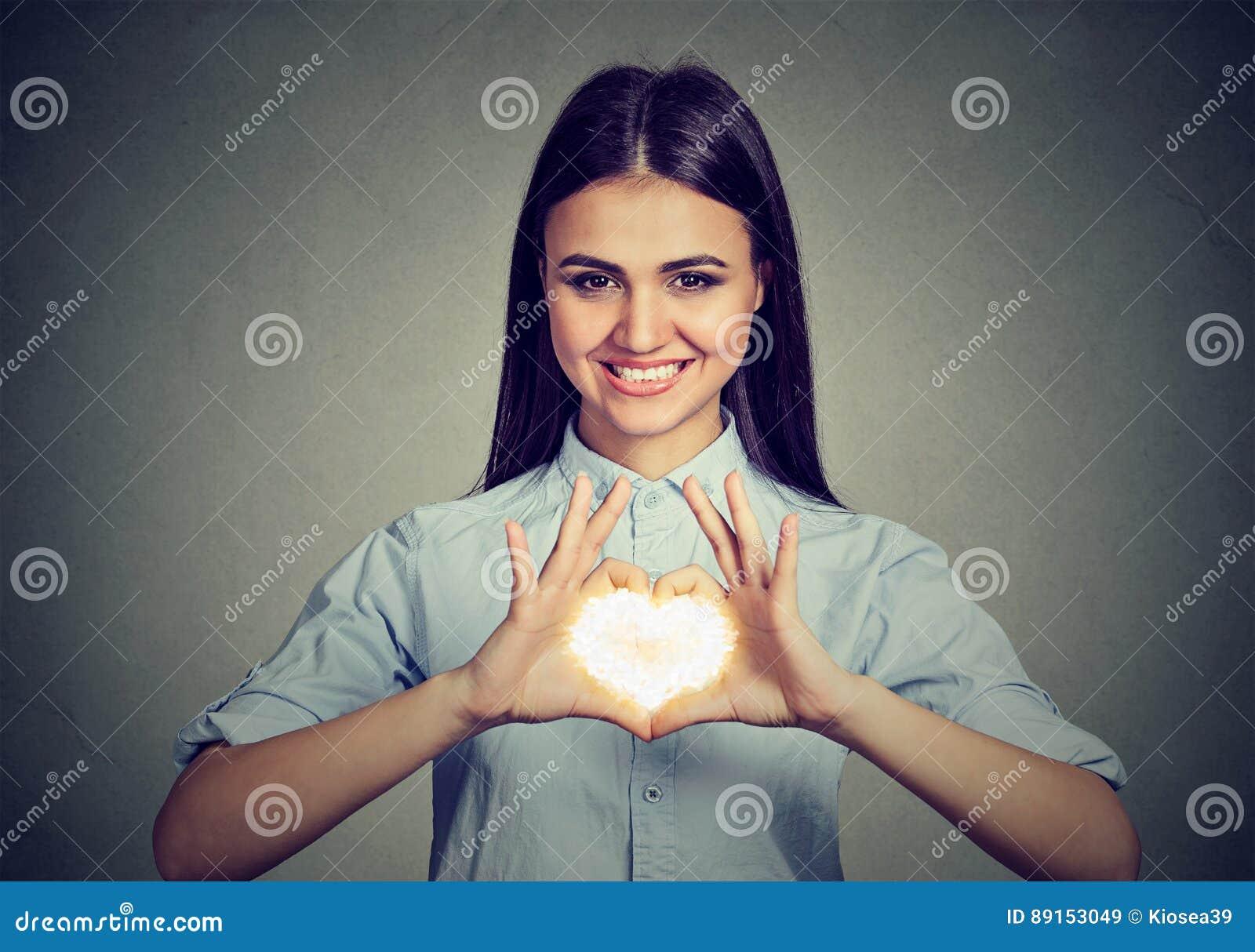 Mulher alegre que faz o sinal do coração com mãos