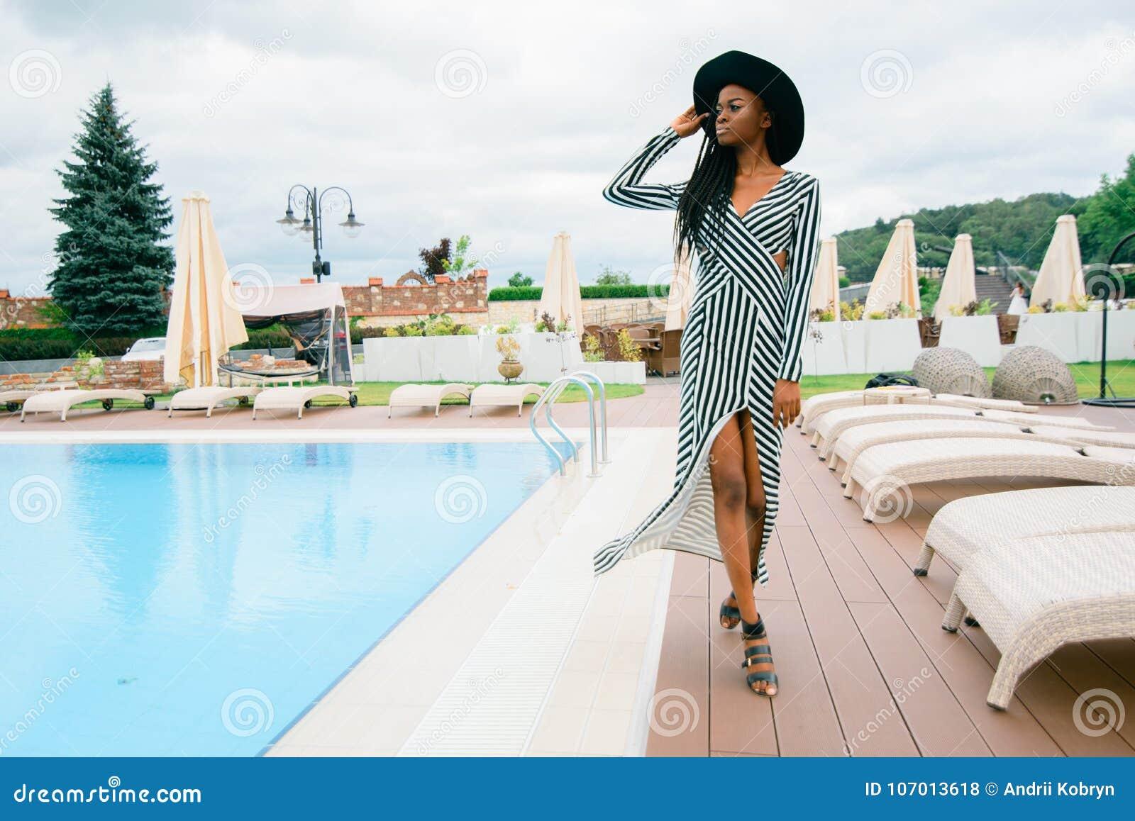 Mulher americana atrativa, bonita, macia, bonita no vestido longo nas listras e chapéu negro Passeio modelo perto da associação d