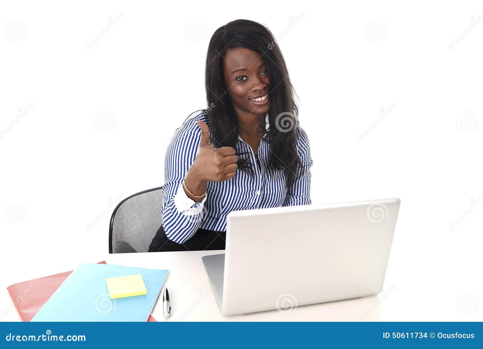 Mulher americana da afiliação étnica do africano negro que trabalha no portátil do computador no sorriso da mesa de escritório fe