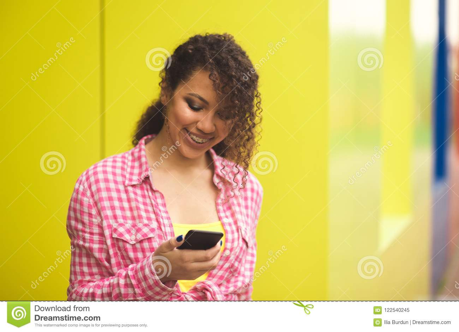 Mulher americana de África que recebe a boa notícia no telefone fora