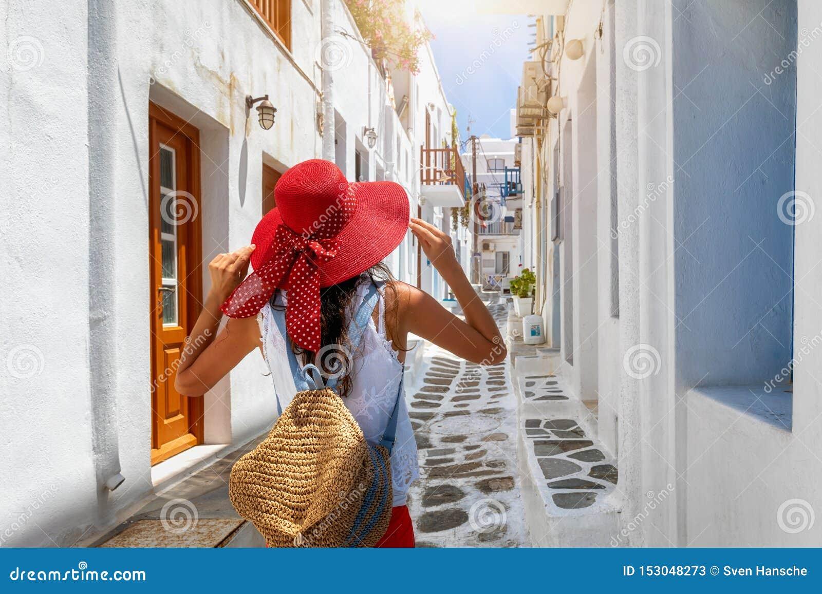 A mulher anda através das aleias da cidade de Mykonos, Cyclades, Grécia