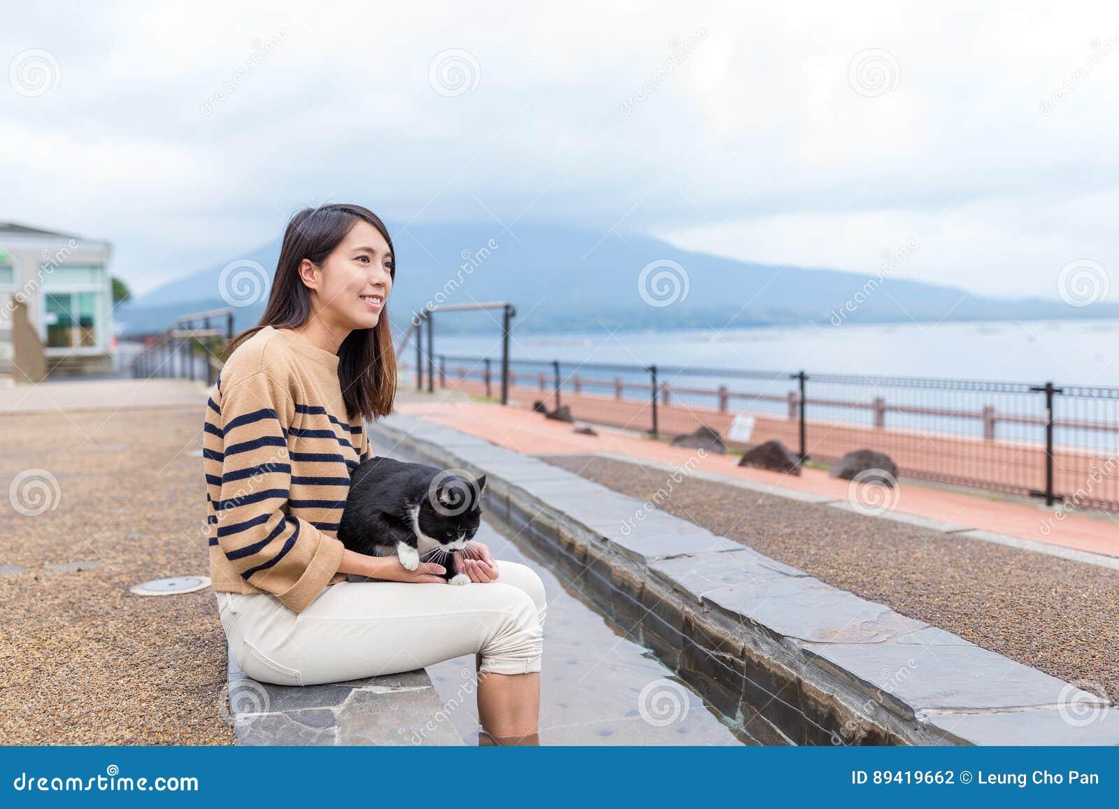 A mulher aprecia o pé onsen com o gato em exterior