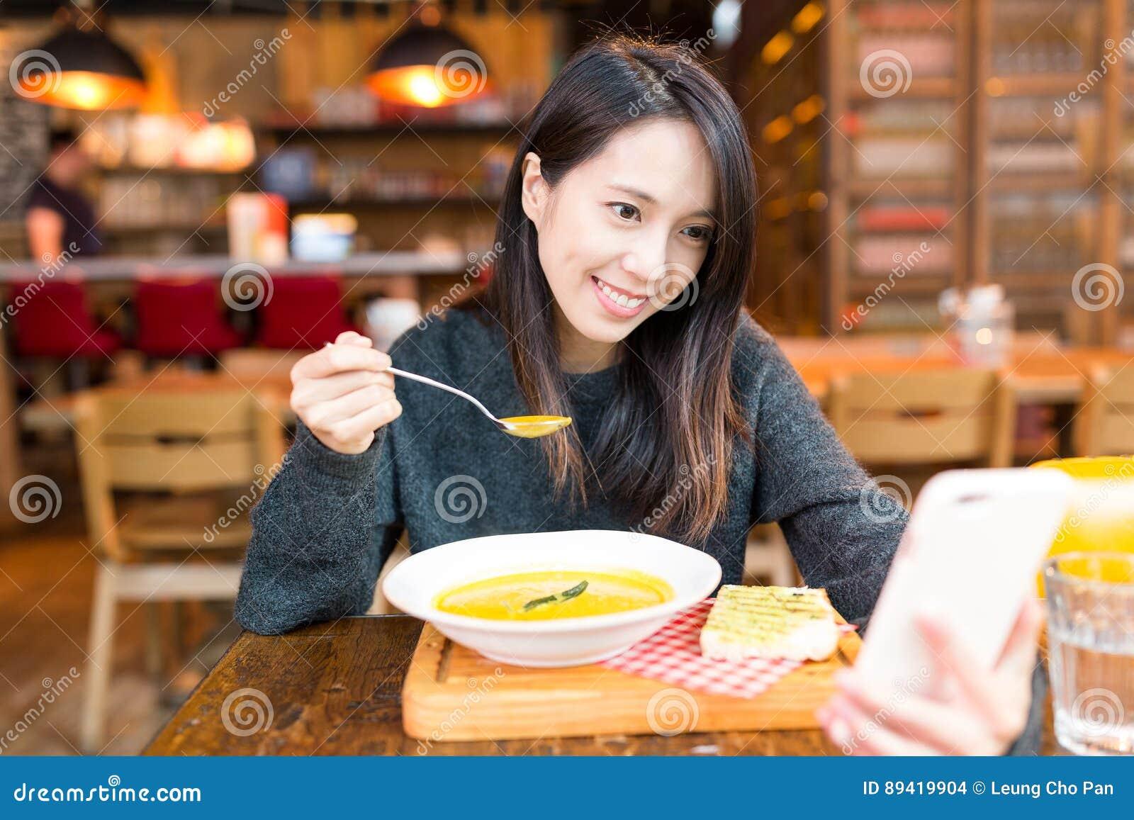A mulher aprecia sua sopa e selfie da tomada