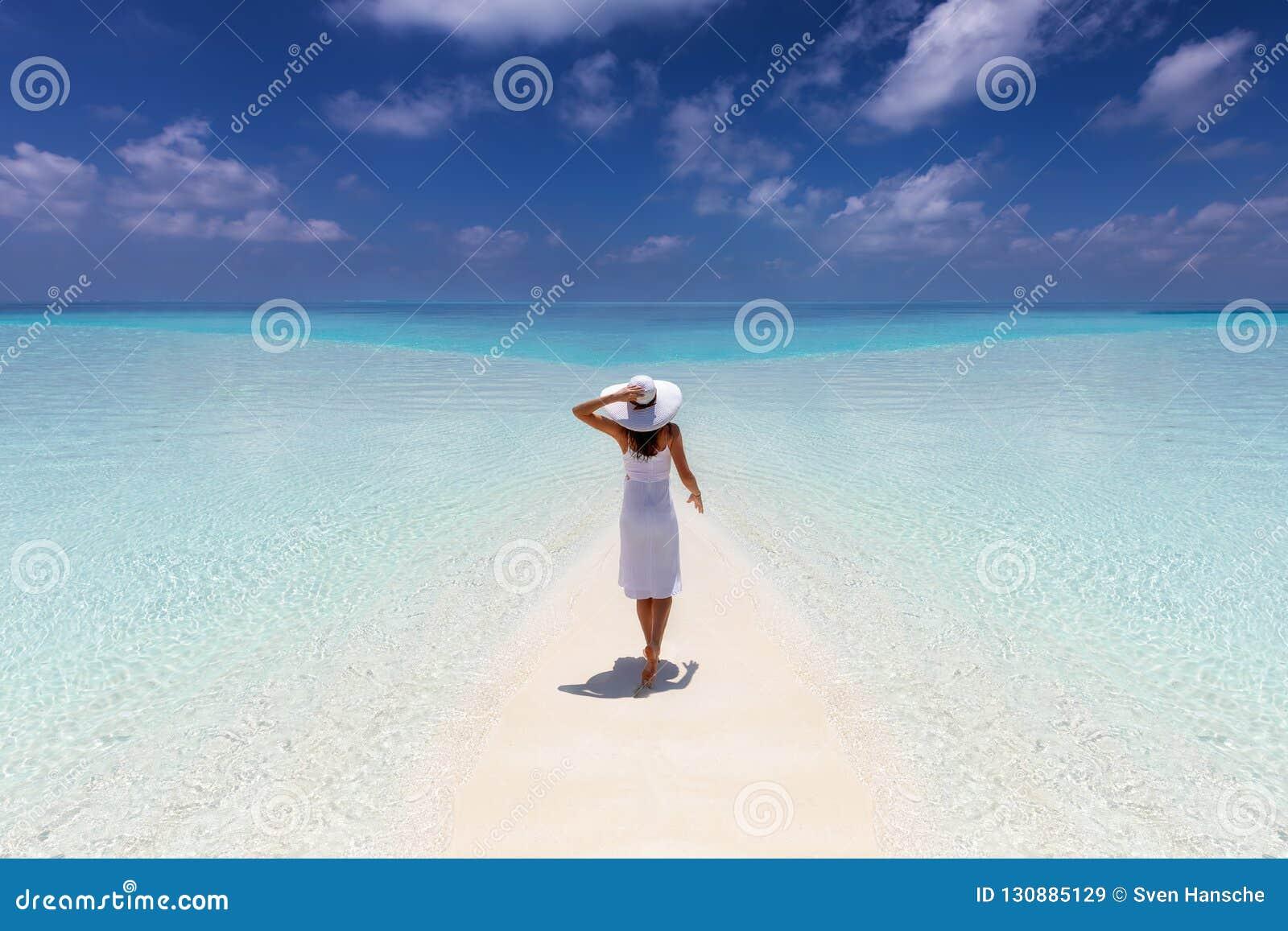 A mulher aprecia suas férias tropicais em uma praia do paraíso