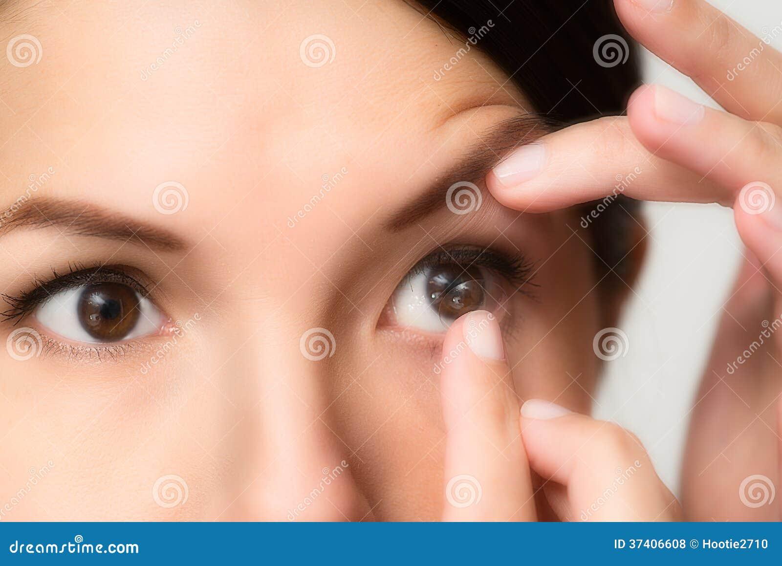 Mulher aproximadamente para colocar uma lente de contato plástica  descartável em seu olho para corrigir sua visão quando a tiver equilibrada  na extremidade ... 5ca2f04c80
