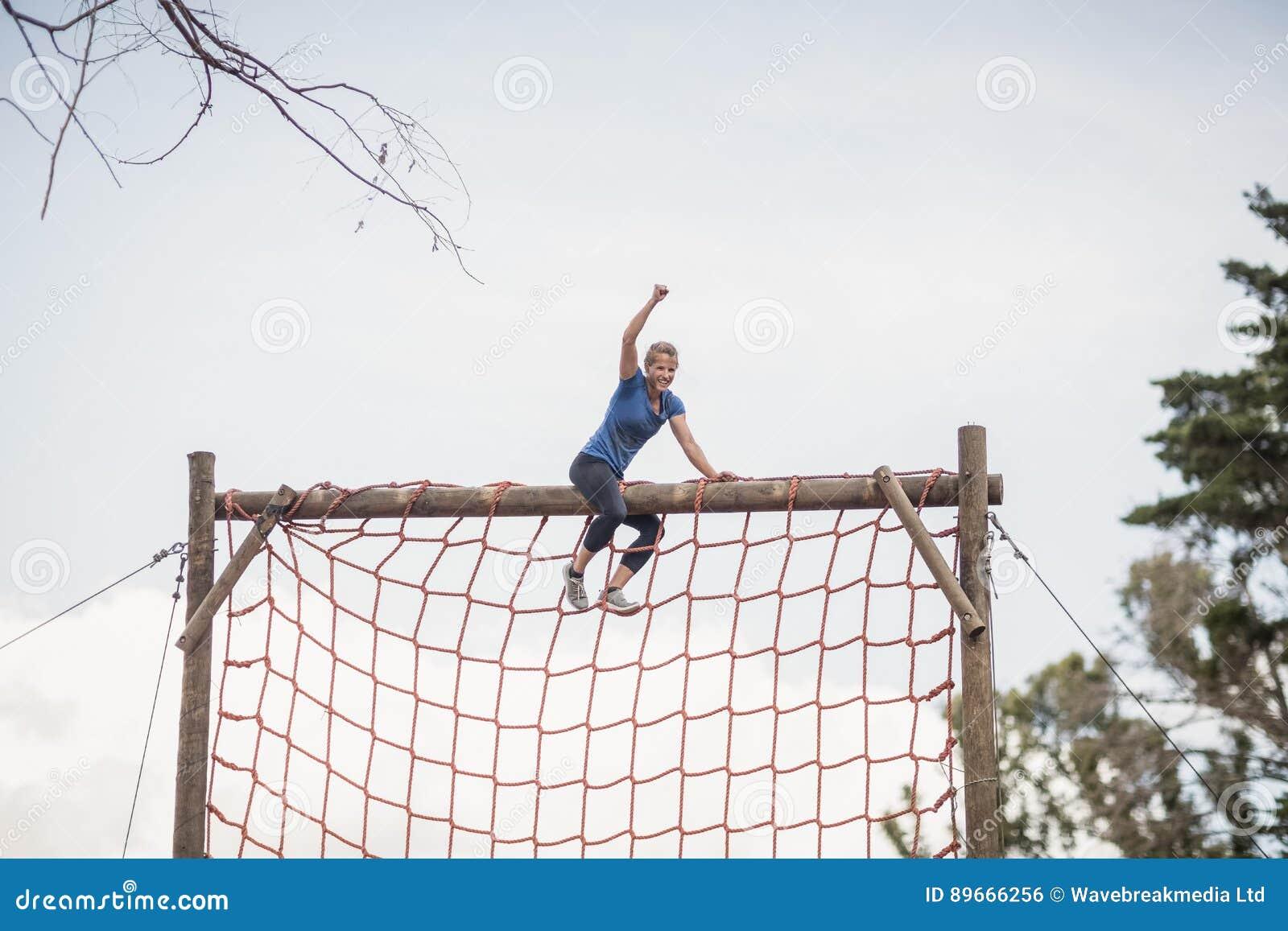 A mulher apta com mão levantou a comemoração do sucesso durante o curso de obstáculo
