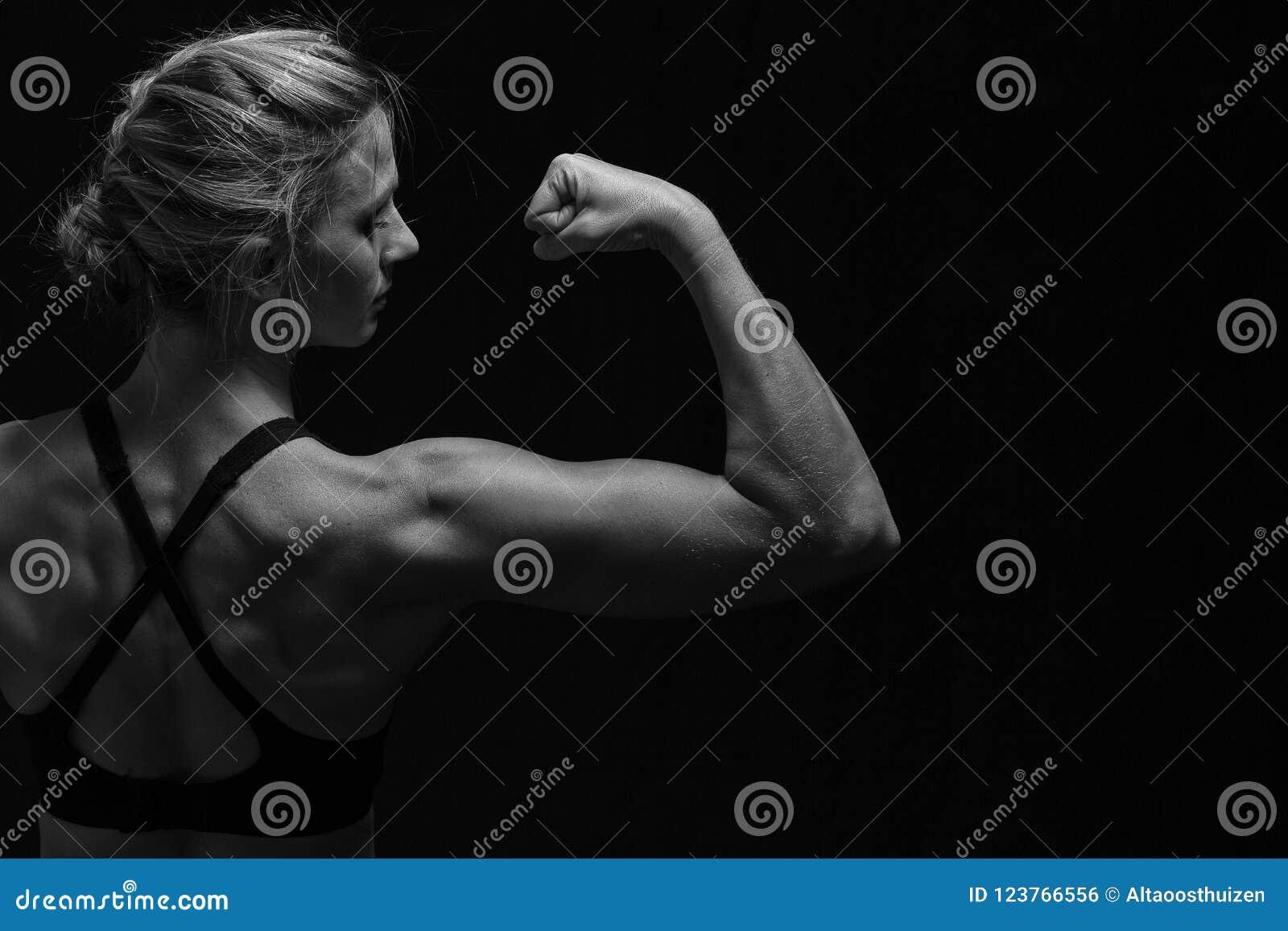 A mulher apta com músculos dados forma suporta sobre na conversão artística