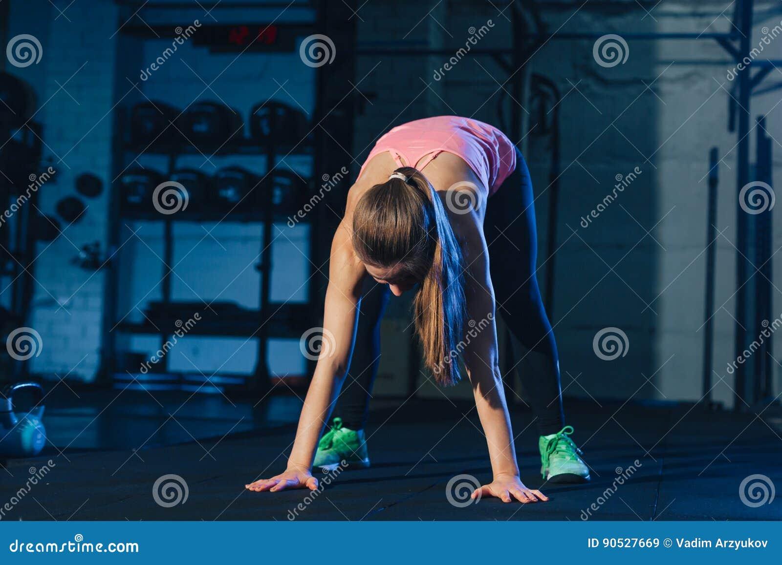Mulher apta no sportswear colorido que faz burpees em uma esteira do exercício em um tipo industrial sujo espaço