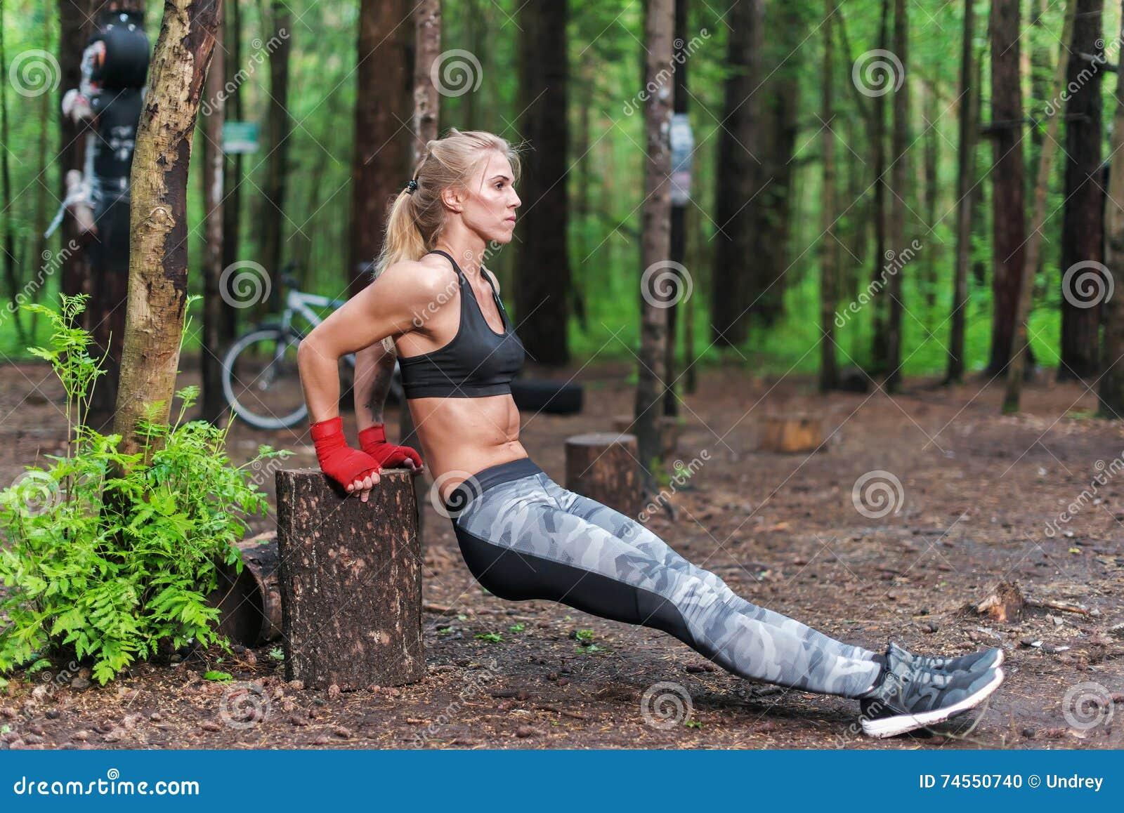Mulher apta que faz mergulhos do tríceps no parque Menina da aptidão que exercita fora com próprio peso do corpo