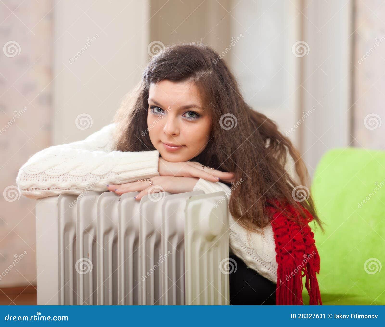 A mulher aquece-se perto do calefator