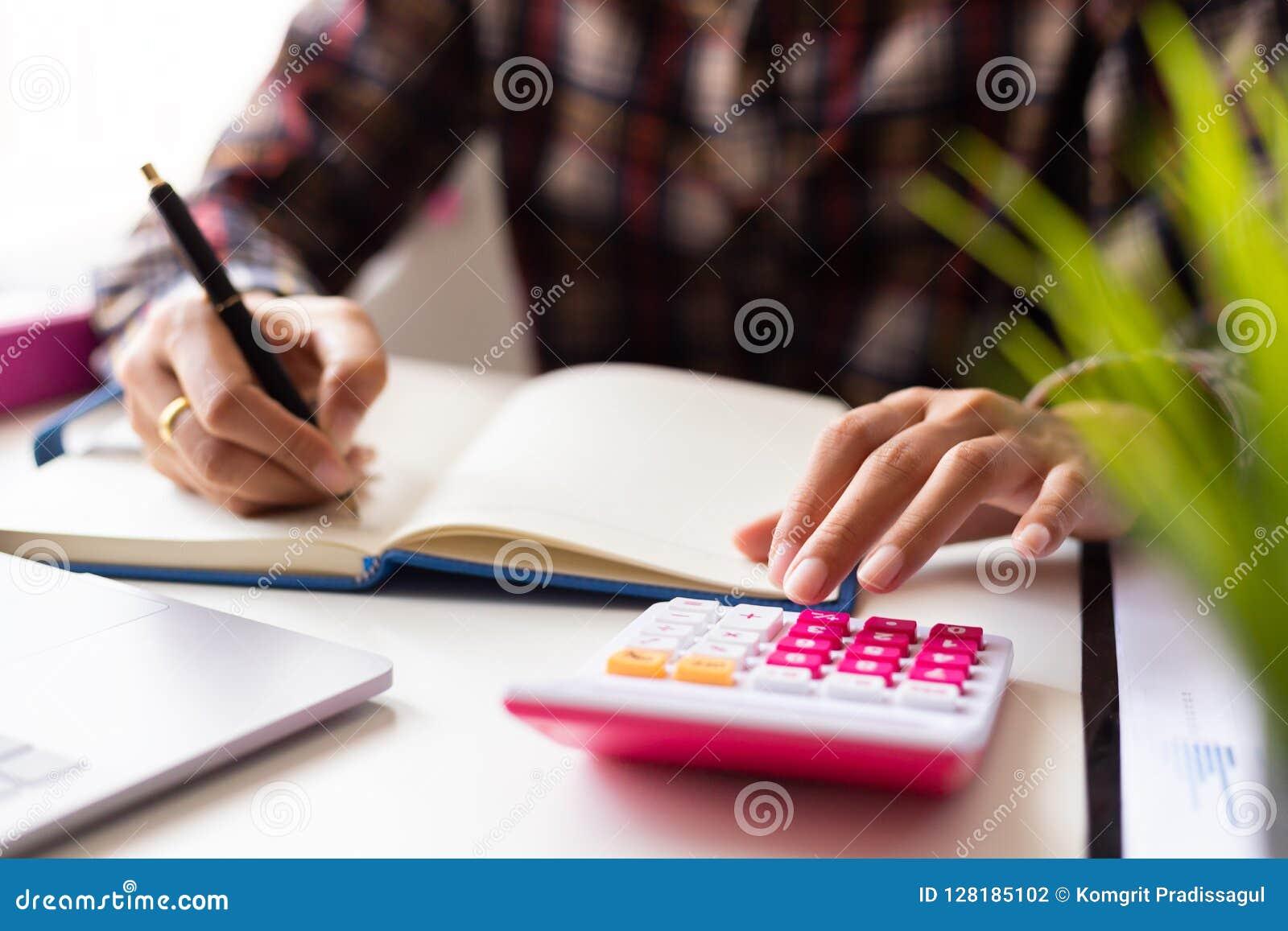 Mulher ascendente fechado que calcula sobre o relatório da finança