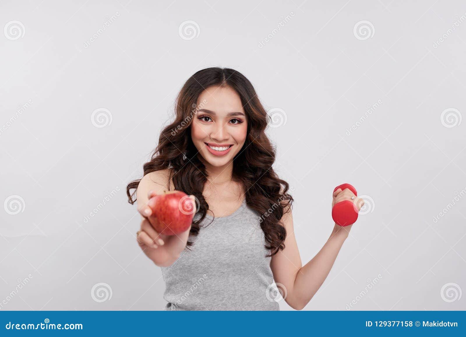 Mulher asiática alegre nova que guarda pesos e a maçã vermelha