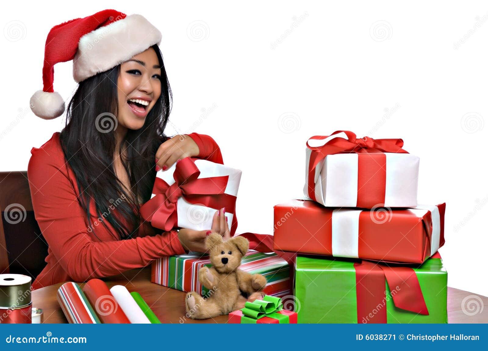 A mulher asiática bonita envolve presentes de Natal