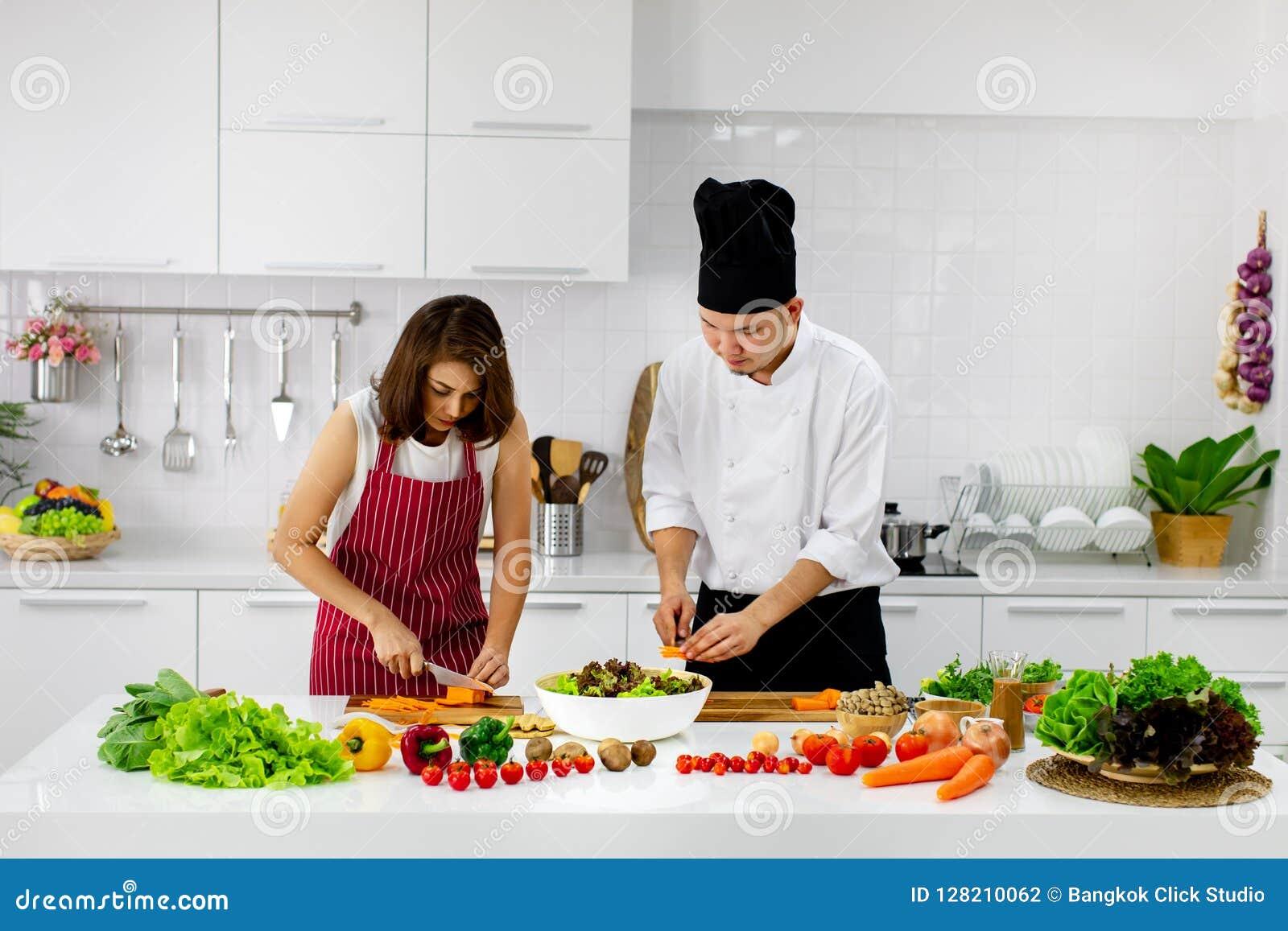 Mulher asiática bonita no avental vermelho que aprende como cozinhar e misturar