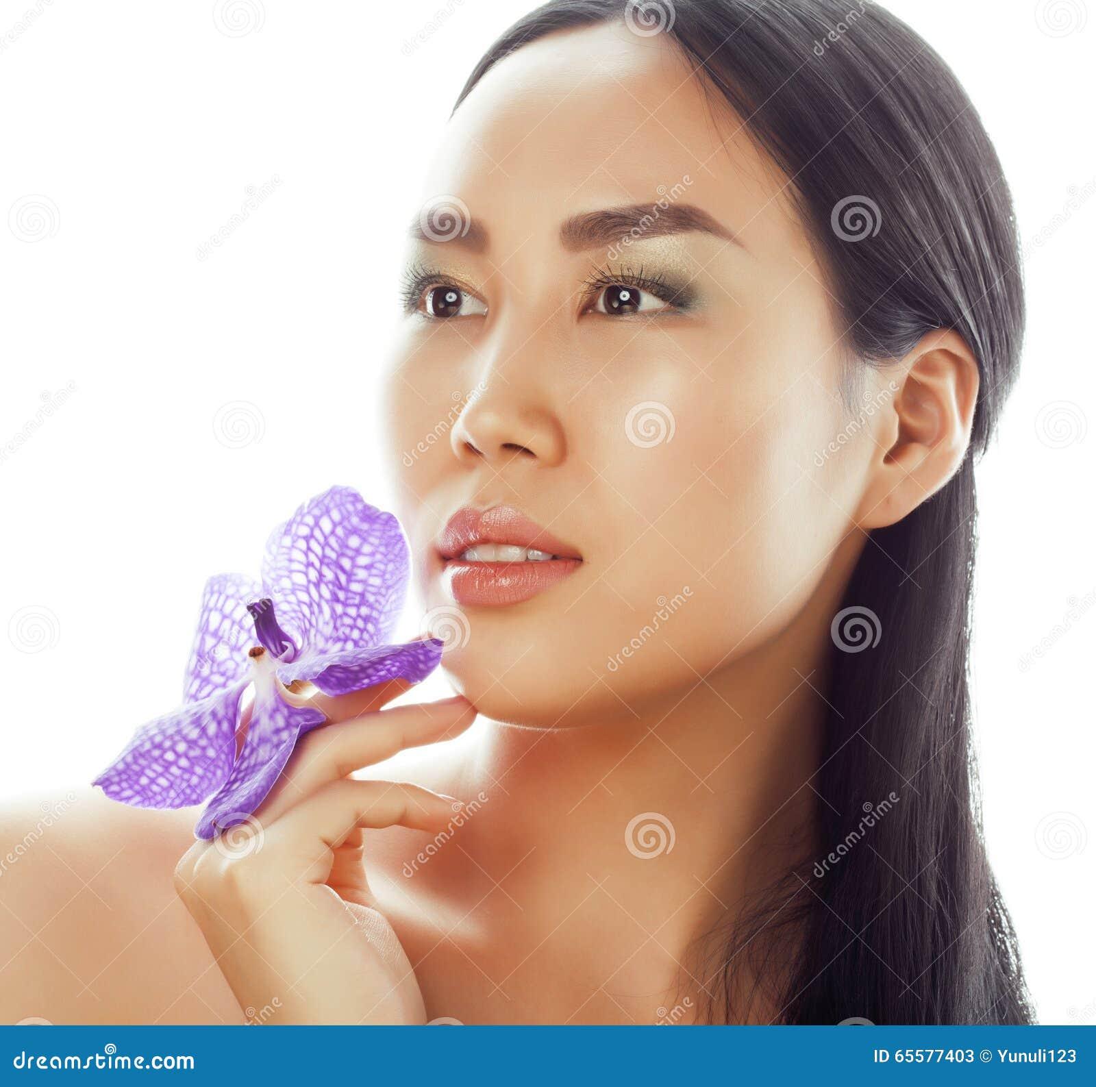 A mulher asiática bonita nova com fim da orquídea da flor isolou acima termas