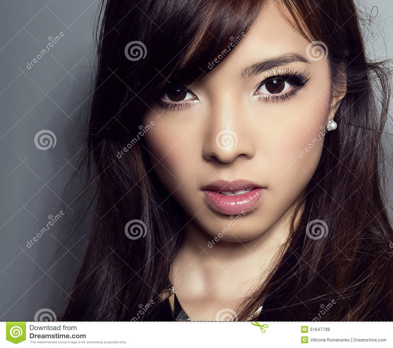 Mulher asiática bonita nova com pele sem falhas e cabelo perfeito do composição e o marrom