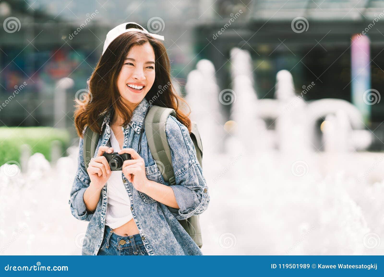 Mulher asiática bonita nova do viajante da trouxa que usa a câmera compacta digital e o sorriso, olhando o espaço da cópia