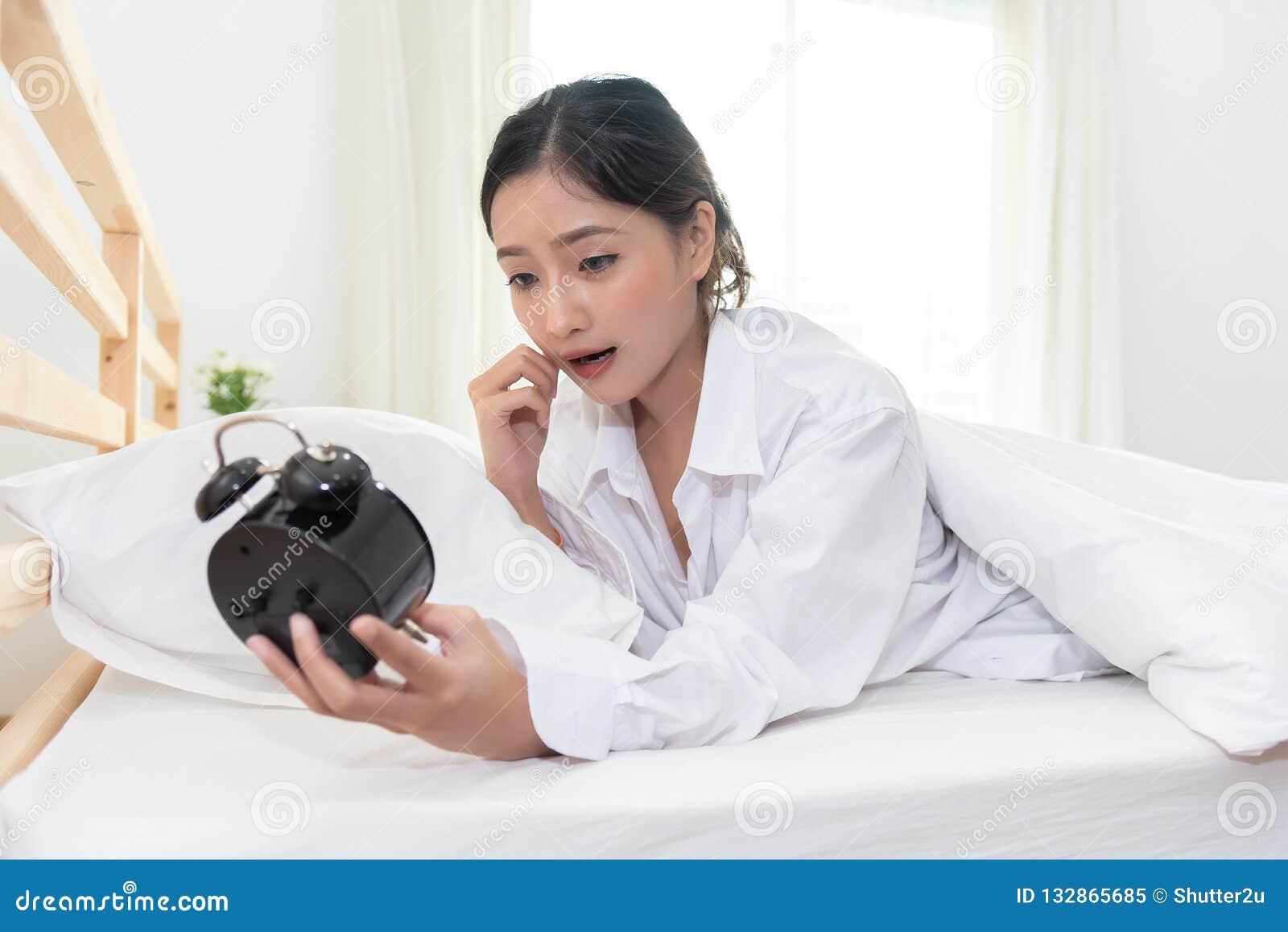 Mulher asiática chocada quando acorde tarde perto para esquecer a ajustar o alarme