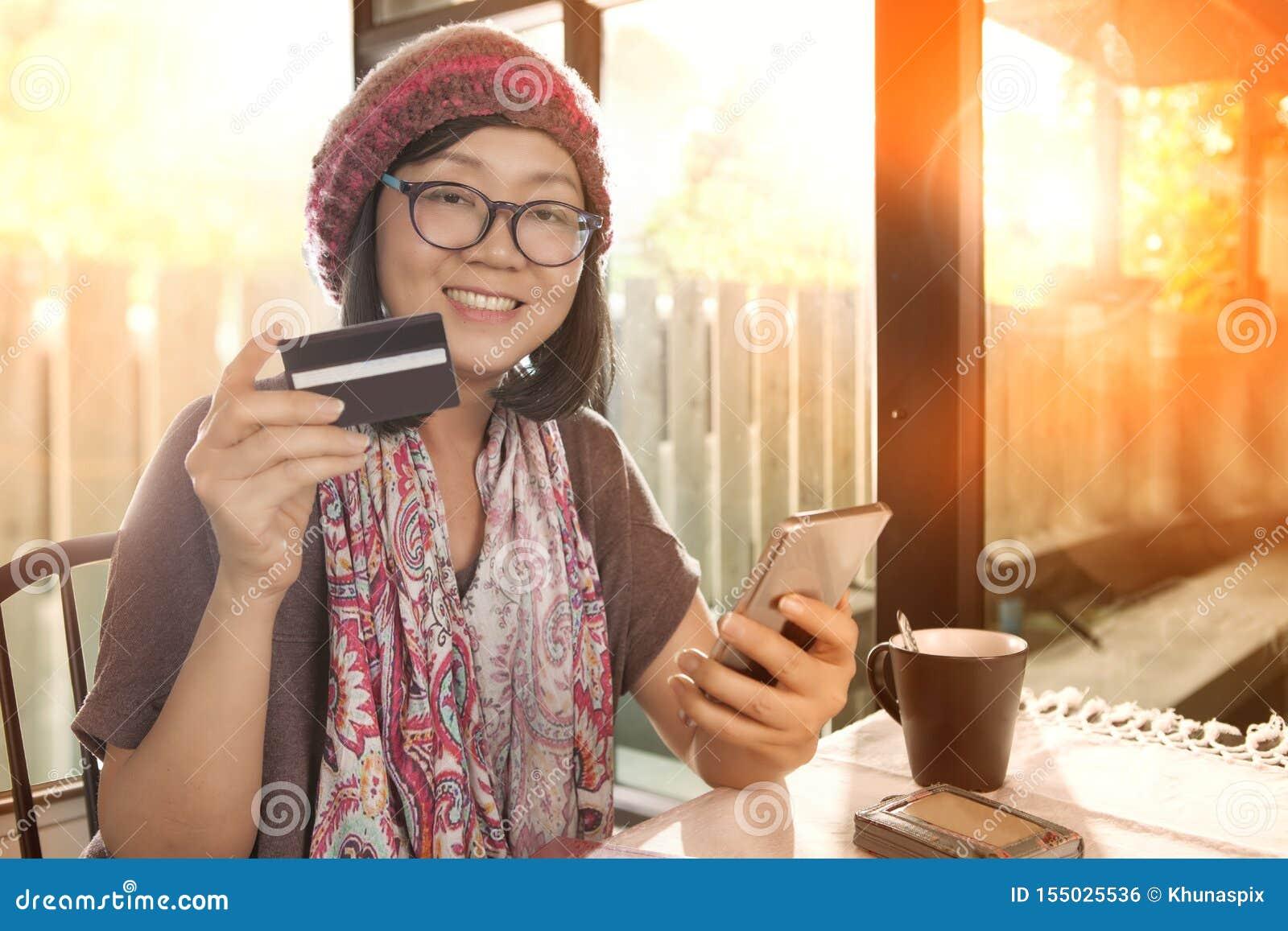 Mulher asiática com cartão de crédito à disposição, compra moderna do estilo de vida na linha
