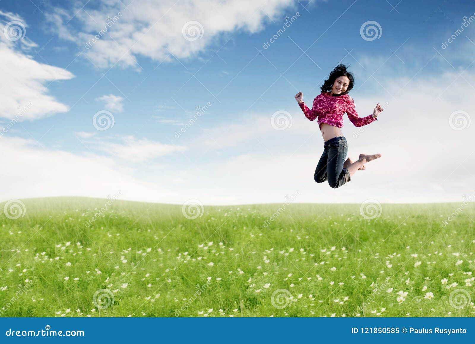 Mulher asiática despreocupada que faz um salto grande no prado