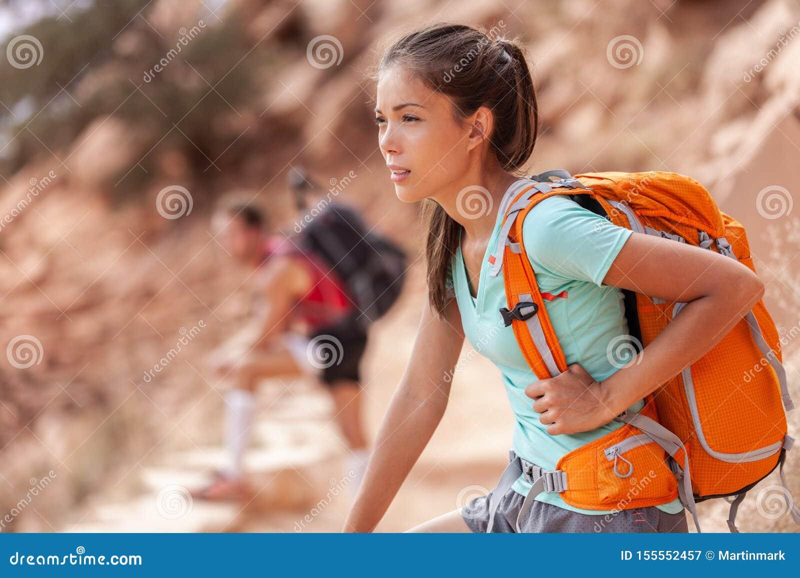 Mulher asiática do caminhante do curso da caminhada que leva a trouxa pesada cansado no passeio na montanha exterior na fuga de G
