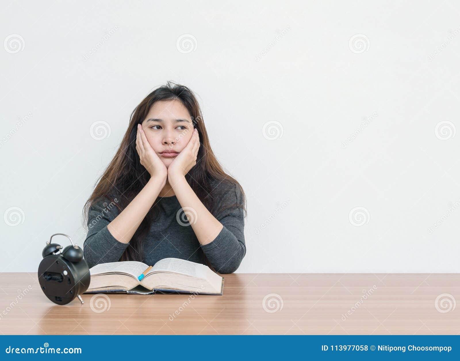 A mulher asiática do close up que senta-se para leu um livro com emoção furada e a cara de pensamento na parede da tabela de made