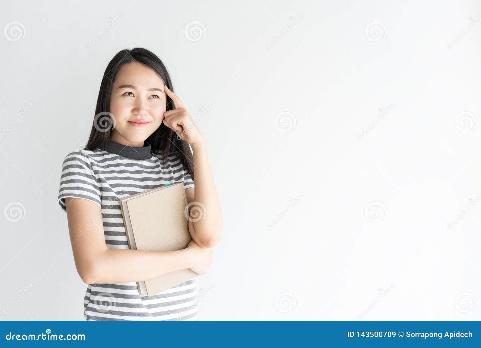 Mulher asiática do retrato que pensa e que guarda o caderno no espaço branco do fundo e da cópia