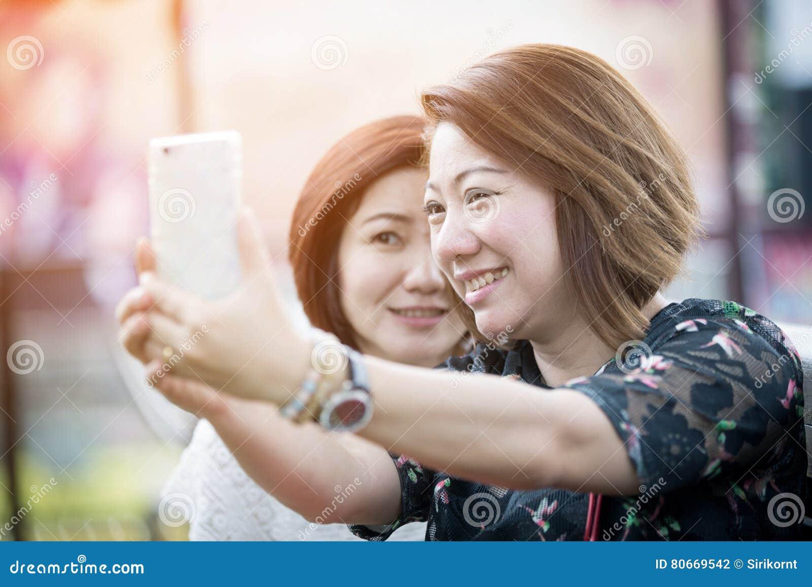Mulher asiática feliz com o amigo que toma um selfie