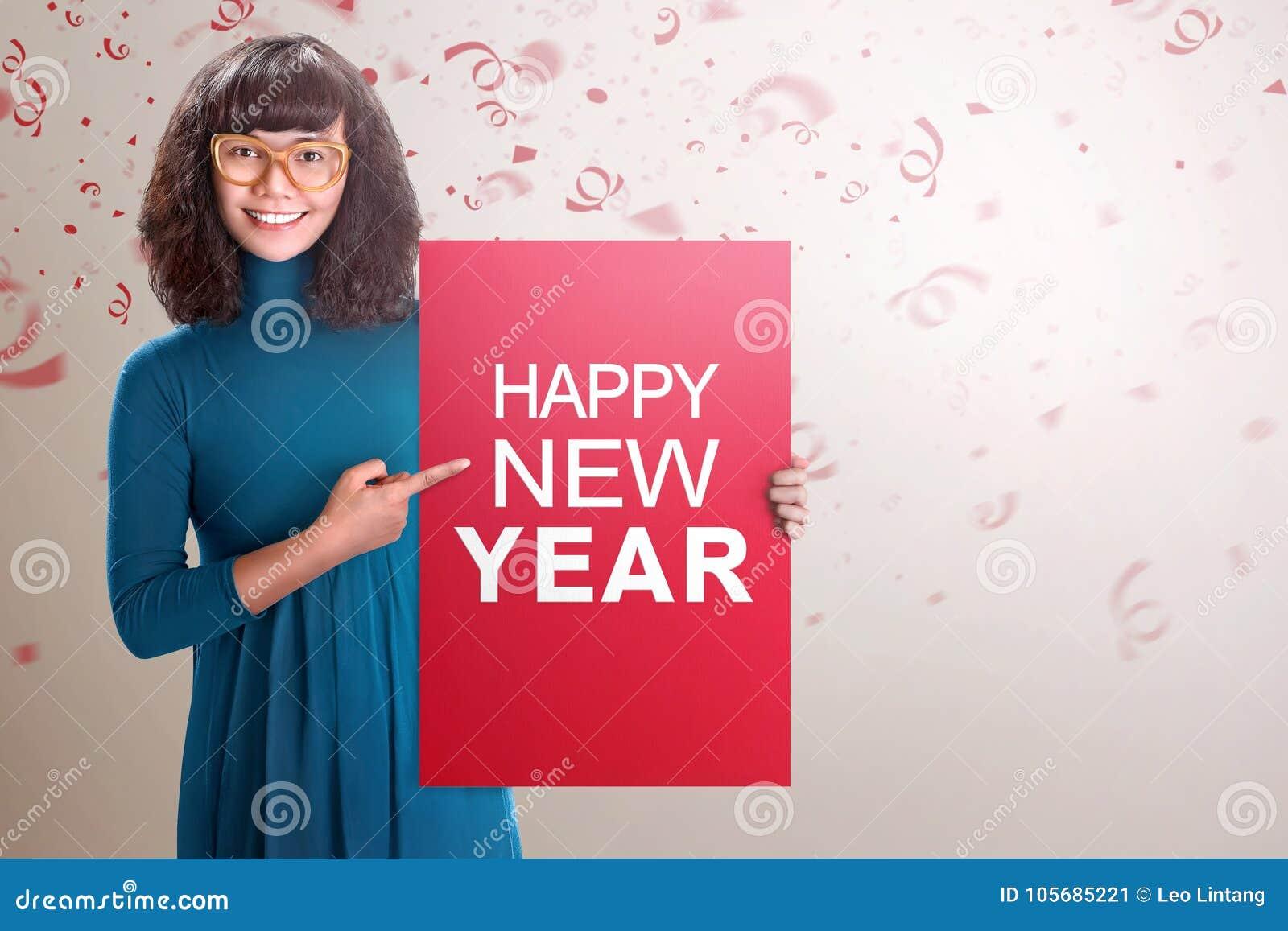 Mulher asiática feliz que mostra a placa vermelha com texto do ano novo feliz