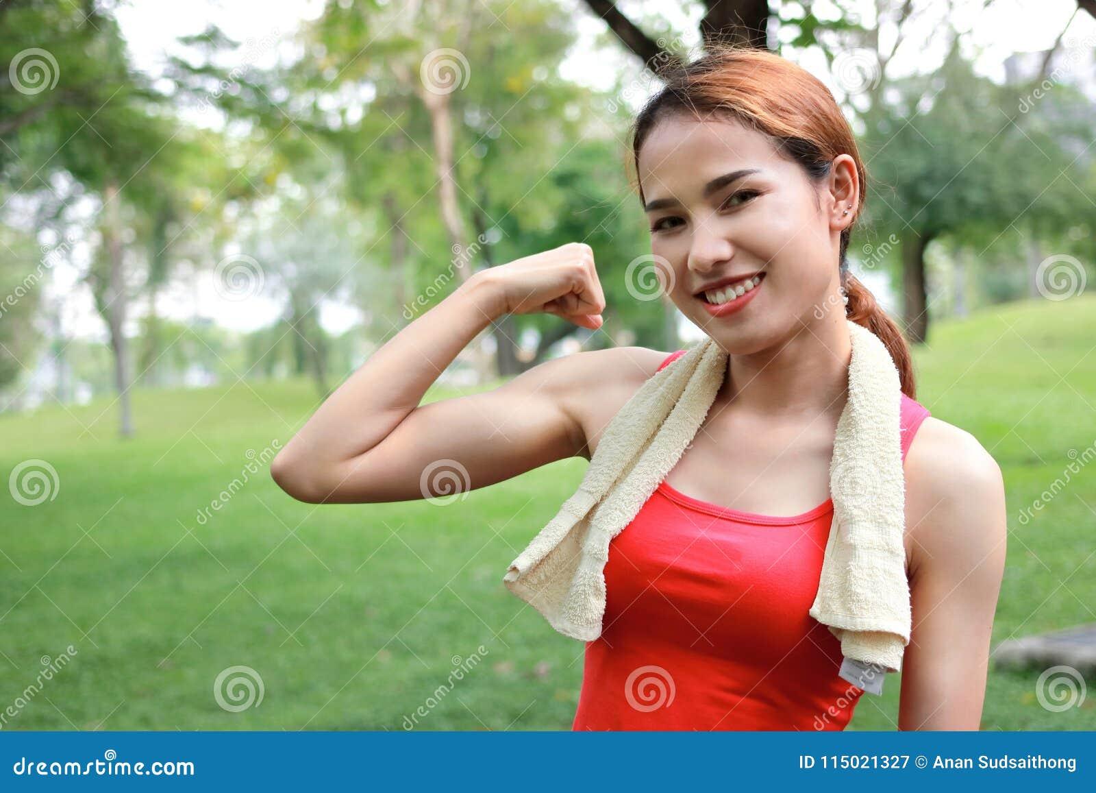 Mulher asiática forte saudável no sportswear vermelho que mostra suas mãos no parque natural Conceito da aptidão e do estilo de v