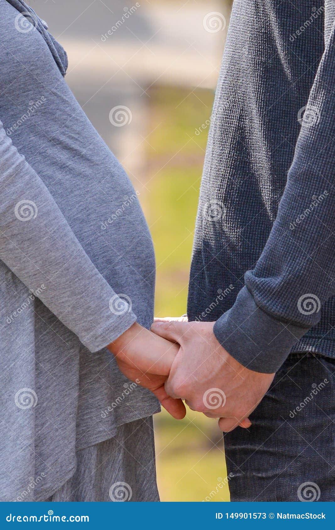 Mulher asiática grávida e pares caucasianos do homem que guardam as mãos que compartilham de um momento antes dos pais tornando-s