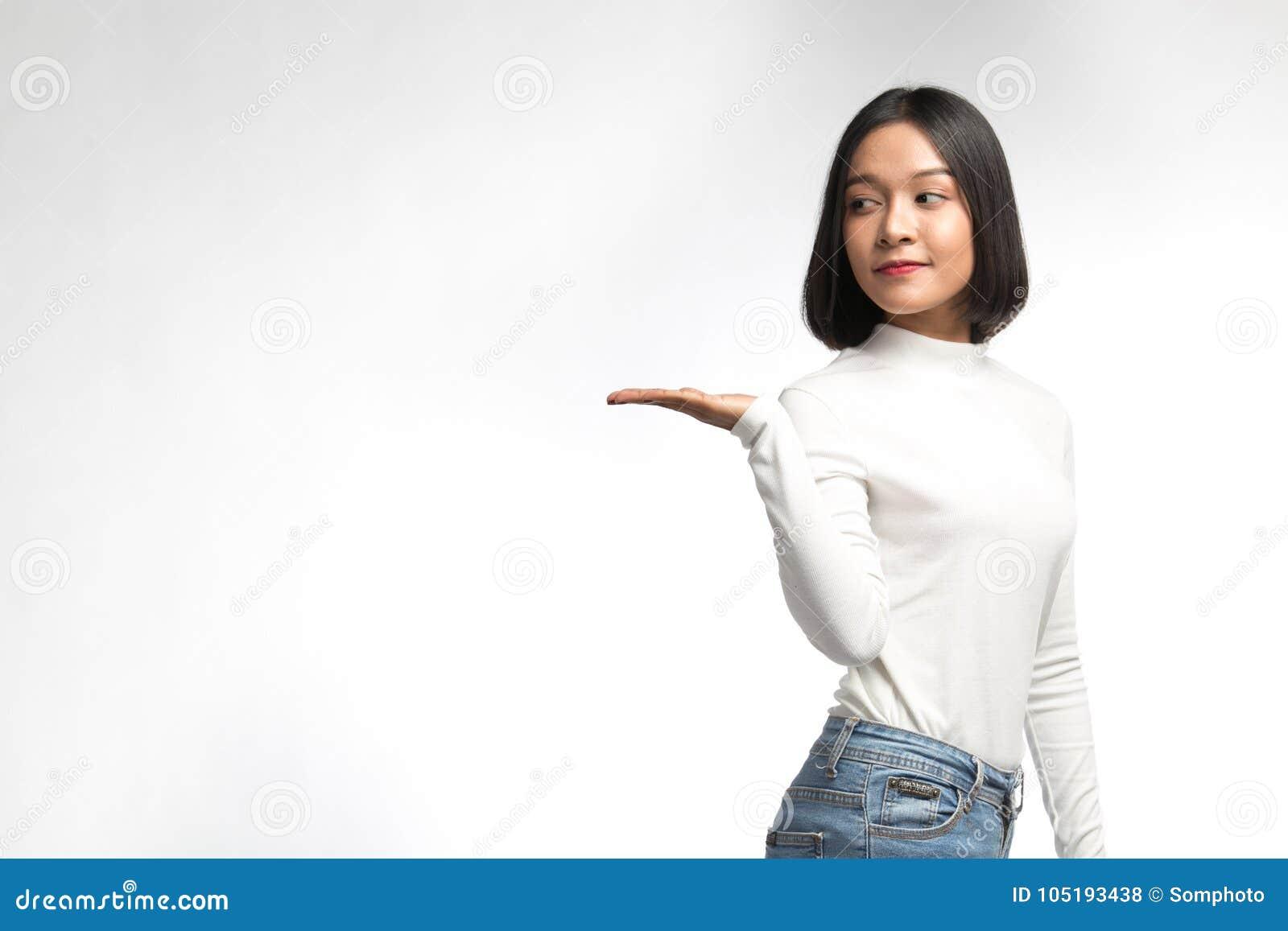 Mulher asiática nova bonita que aponta no whitespace