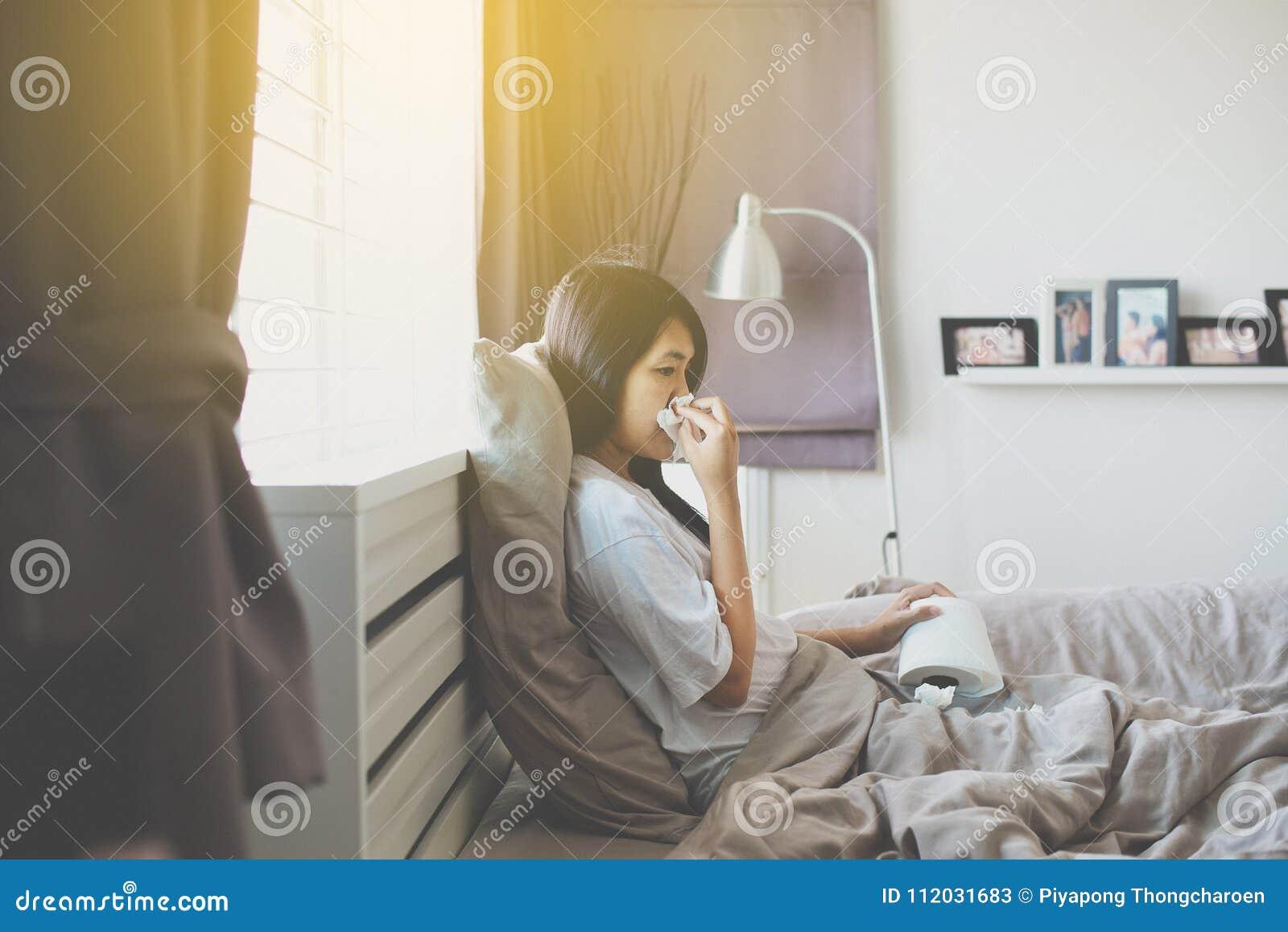 Mulher asiática nova com sopro do frio e nariz ralo na cama, espirrar doente da mulher