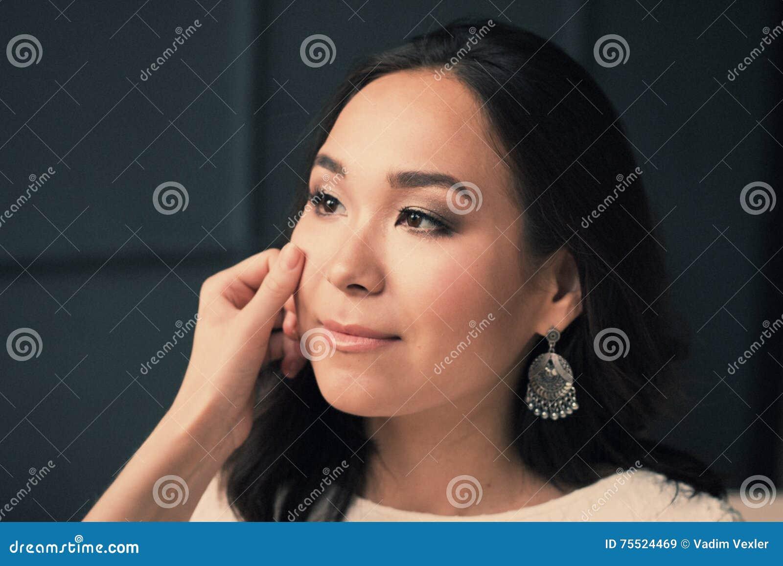 Mulher asiática nova limpe a pele que descansa após o skincare, no fundo escuro cara fresca perfeita dos termas bonitos