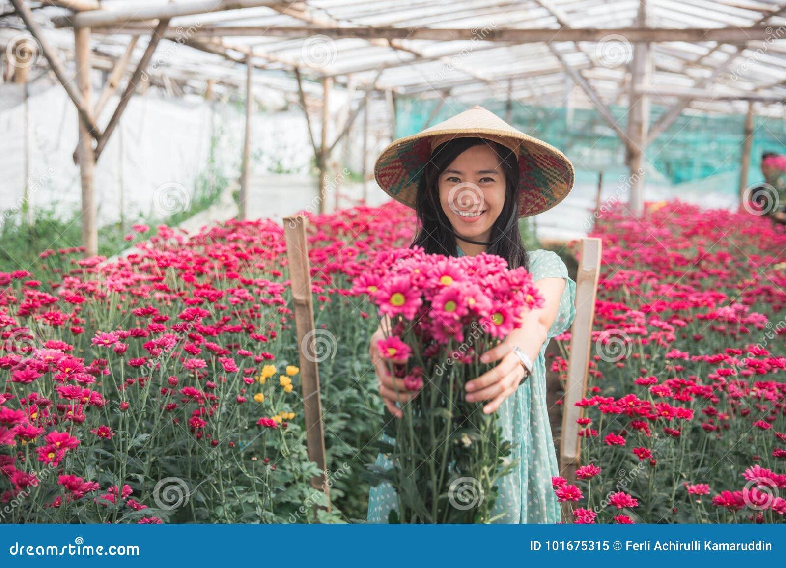 Mulher asiática nova que mostra flores da camomila