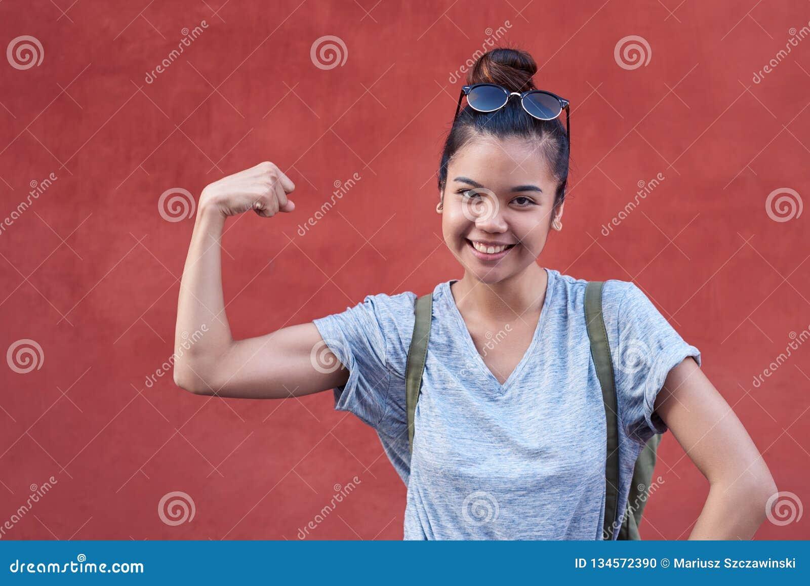 Mulher asiática nova que sorri ao humorously dobrar seu bíceps fora
