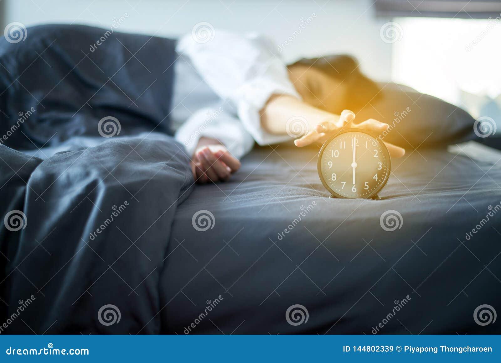 A mulher asiática odeia obter forçada acordando cedo 6 horas na manhã, despertador