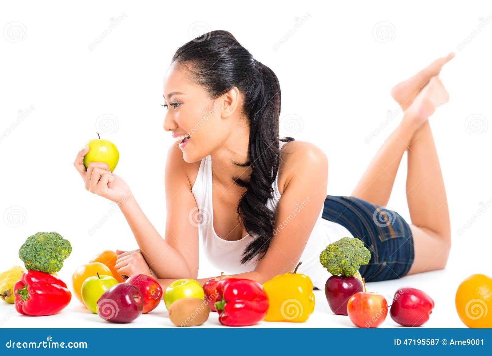 Mulher asiática que come o fruto fresco