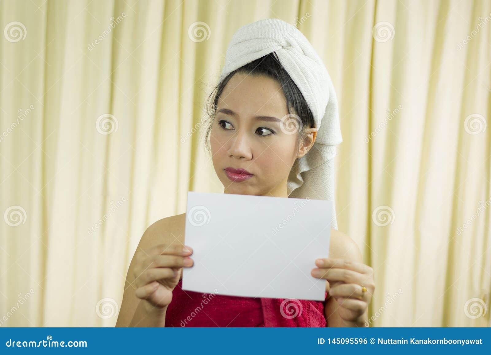 Mulher asiática que guarda a bandeira vazia vazia e a atuação veste uma saia para cobrir seu peito após o cabelo da lavagem,