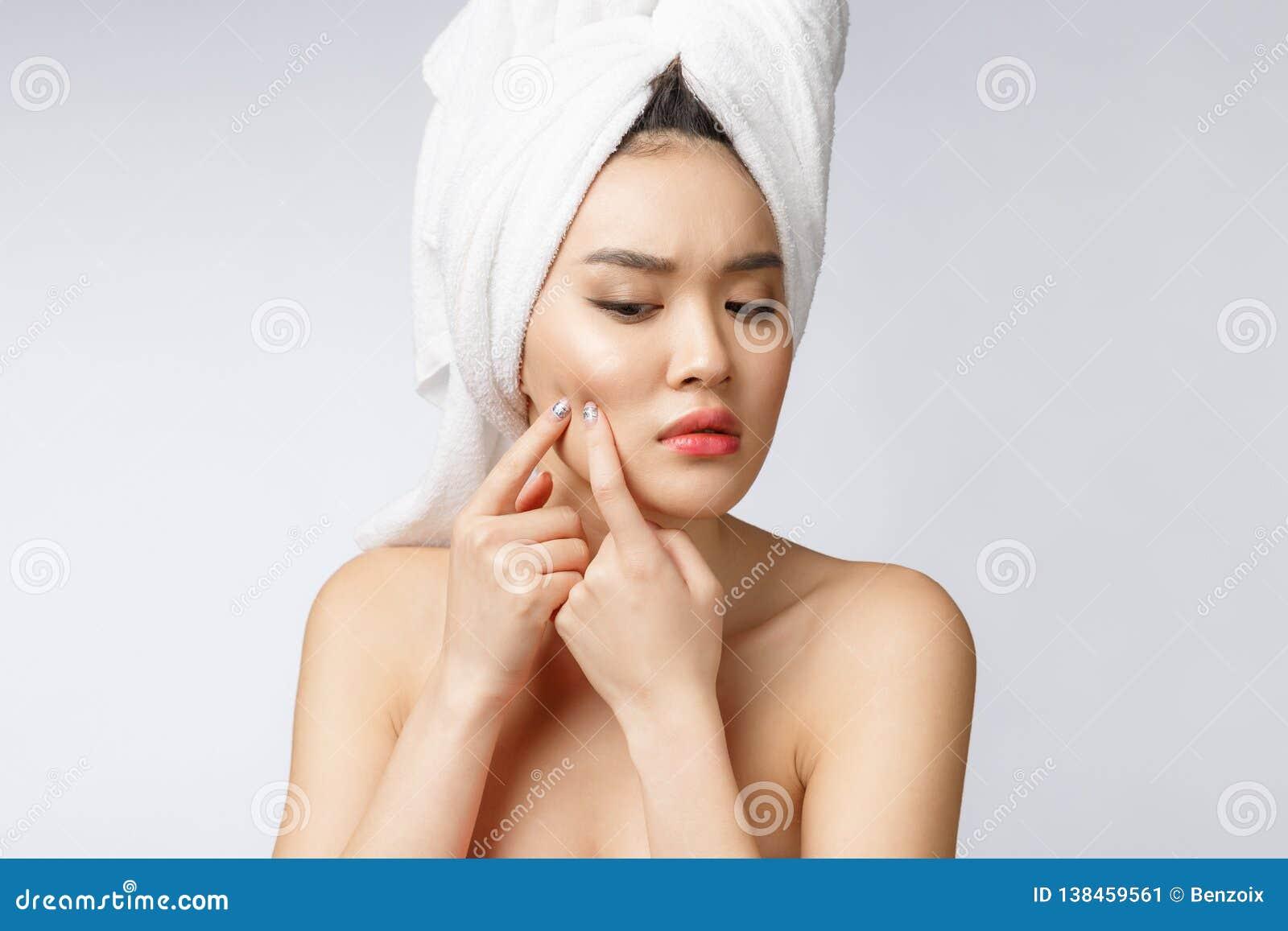 Mulher asiática que olha a espinha na cara A jovem mulher tenta remover sua espinha Conceito do cuidado de pele da mulher Isolado