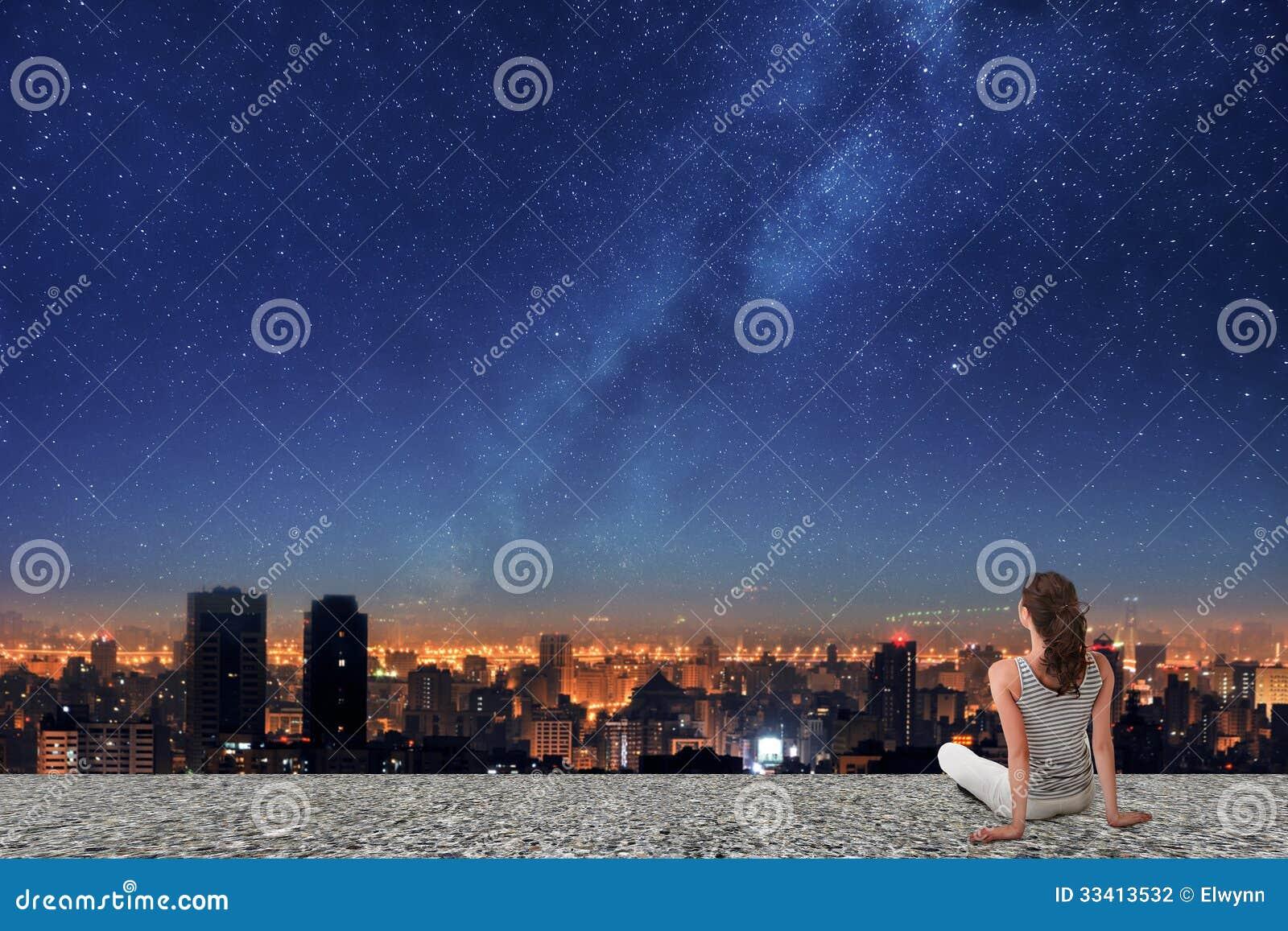 Mulher asiática que olha na cidade da noite