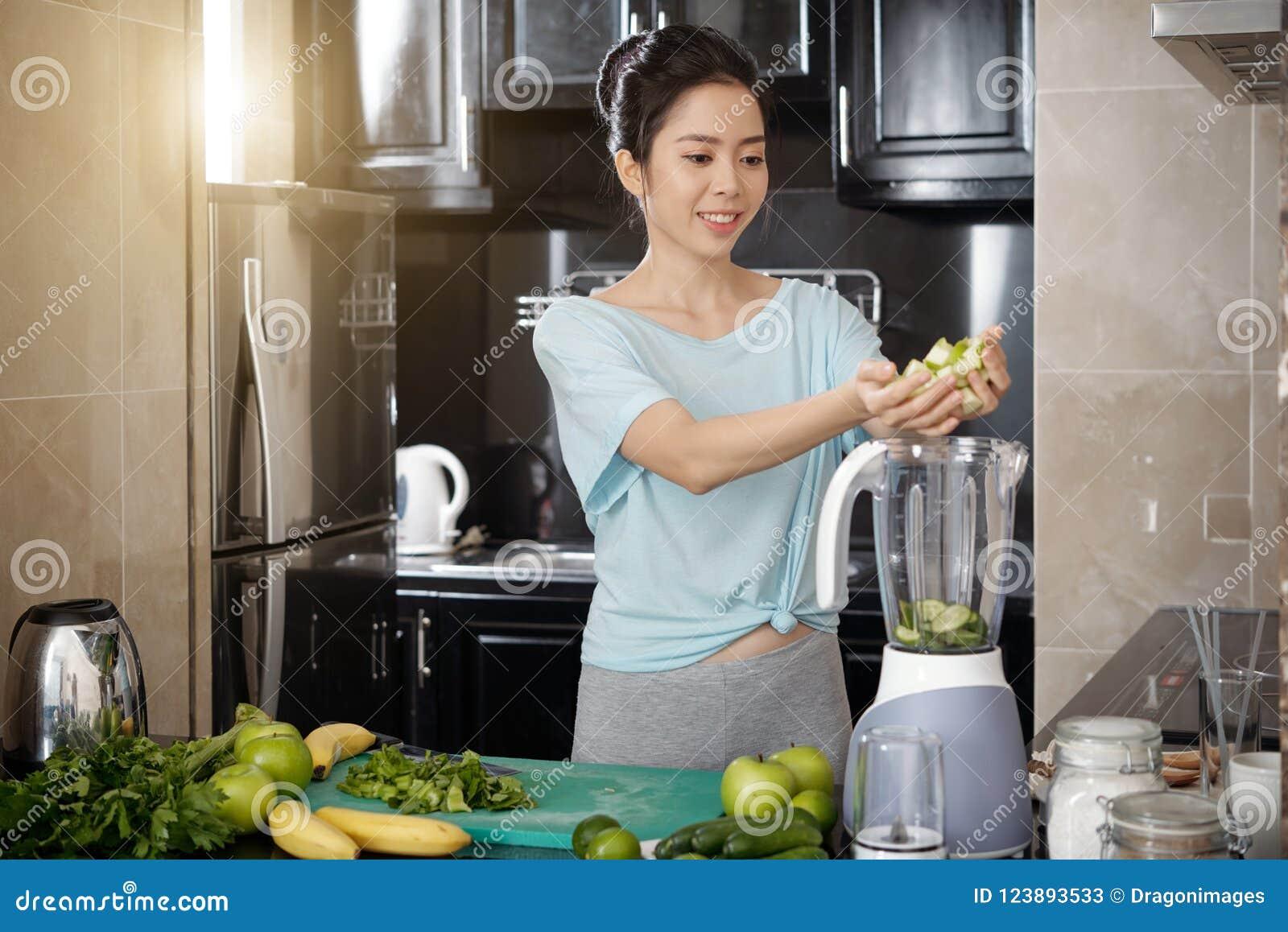 Mulher asiática que põe frutos no misturador