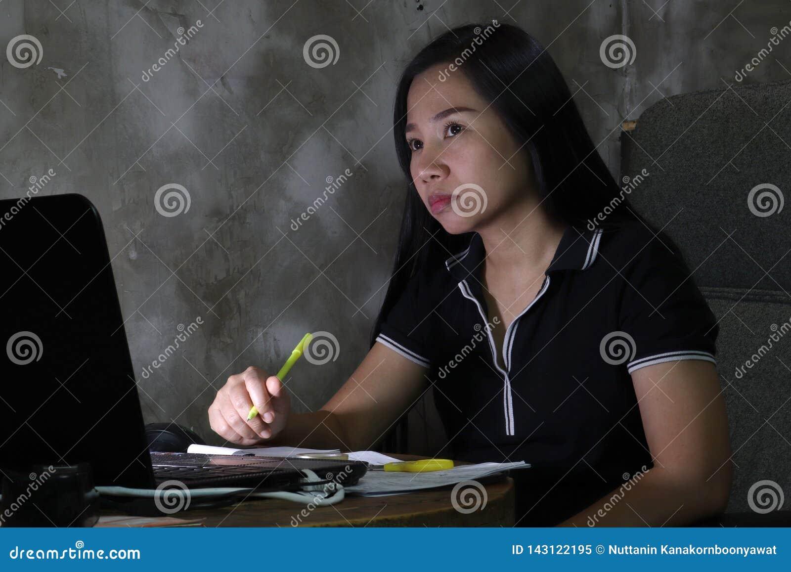 Mulher asiática que trabalha da casa atrasada no trabalho noturno no conceito de iluminação pobre a luz escura tem alguns grão e
