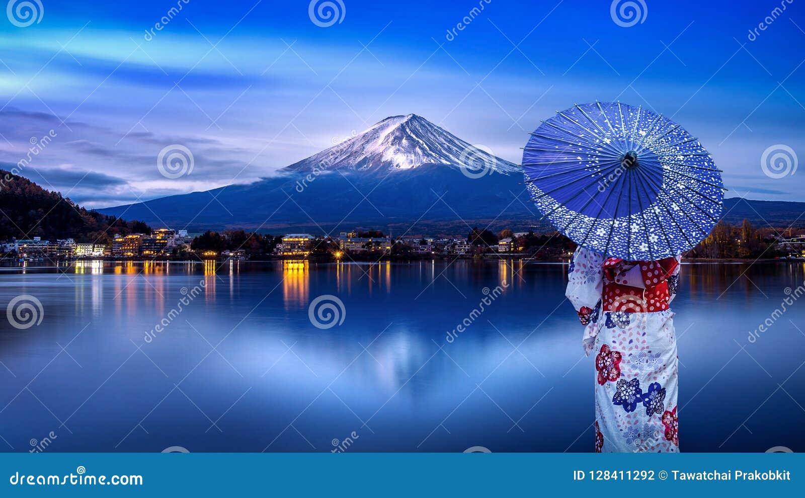 Mulher asiática que veste o quimono tradicional japonês na montanha de Fuji, lago Kawaguchiko em Japão