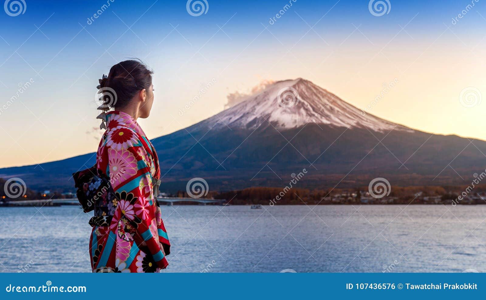 Mulher asiática que veste o quimono tradicional japonês na montanha de Fuji Por do sol no lago Kawaguchiko em Japão
